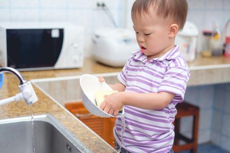 Lindo pequeño niño asiático de 2 años de edad, niño de pie y divirtiéndose lavando los platos, concéntrese en lavar los platos en la cocina en casa, pequeño ayudante de hogar, tareas para niños, concepto de desarrollo infantil