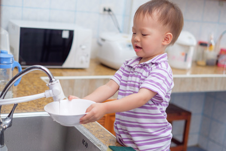 Cute smiling little Asian 2 year old toddler baby boy child standing and having fun doing the dishes / washing dishes in kitchen at home, Little home helper, chores for kids, child development concept 版權商用圖片