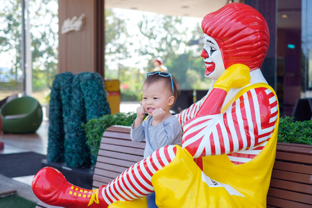 Nakhon Sawan, THAILAND - Feb 01, 2018: Happy cute little Asian toddler boy child play with Ronald McDonald in front of McCafé, McCafé is a coffee-house-style food & beverage chain, owned by McDonald's Redakční