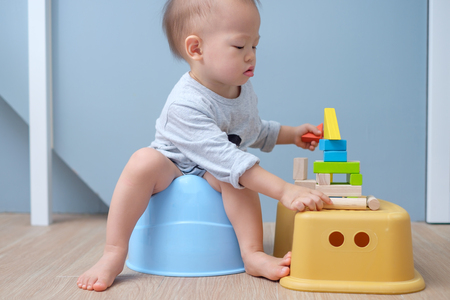 Cute little Asian 18 months old  1 year old toddler baby boy child sitting on potty playing with wooden blocks toy. Kid playing with educational toy & Toilet training concept. - Selective focus