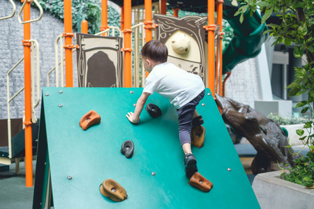 Cute Asian 2 - 3 years old toddler child having fun trying to climb on artificial boulders at indoor playground, Little boy climbing up a rock wall, Hand & Eye Coordination, Motor Skills development Stockfoto