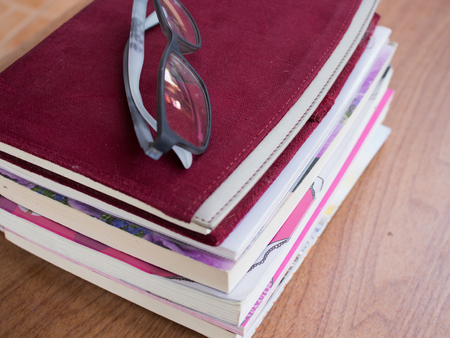 assignments: Stack of books on wooden table Stock Photo