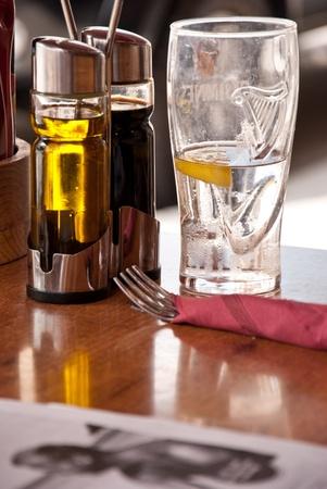Waiting for dinner. On table glass of lemon water, knife, fork and bottle of oil.