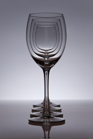 Four empty wine glasses in line. Grey table and background. Light from behind.