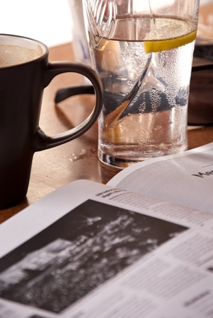 Reading newspaper in coffee-house during break. On the table glass of lemon water and coffee mug. In foreground newspaper.