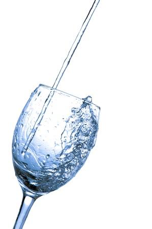 A água doce derramado no vidro de vinho isolado sobre o fundo branco