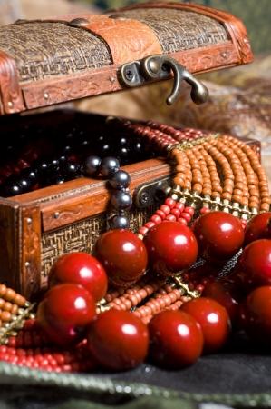 Close-up velho baú de jóias com colares colocados em lenços Muitos colar dentro