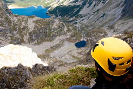 Climber with yellow helmet looking at lake valley in Tatra Mountains, Poland.