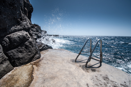 Metal ladder on rocky shore. Wavy sea. Stock Photo