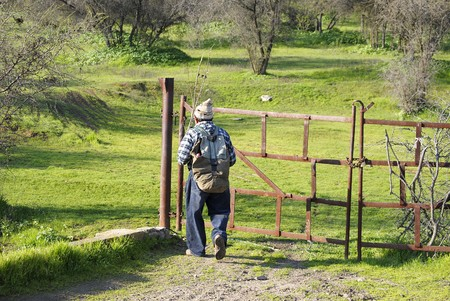 indigent: Beggar walker, with his old backpack and a woolen skullcap the walkerRecurs the paths of the hills and slopes without fixed, single direction walks on the life. Stock Photo