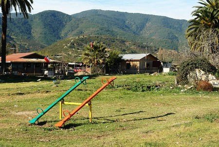 populate: Infantile games with seesaw of colors at rural zone, humble place at agricultural town.
