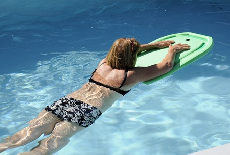 Exercise in water, woman with float