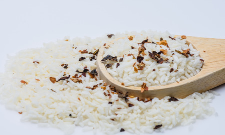 Close up uncooked rice with spices on wooden spoon