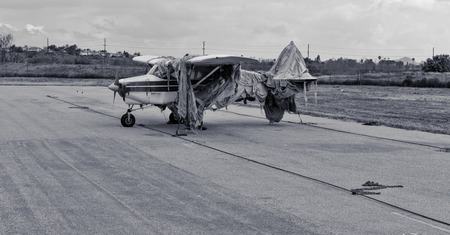 Black and white old airplane covered in burlap rags