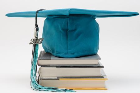 卒業の帽子、タッセルおよび学生のための本