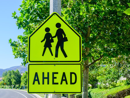 Student crossing ahead with trees in background Stock Photo