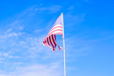 青空と破れたアメリカ国旗