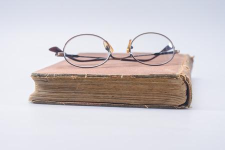 古い茶色の本の老眼鏡