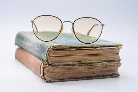 大きな丸い 2 つのビンテージ本に老眼鏡