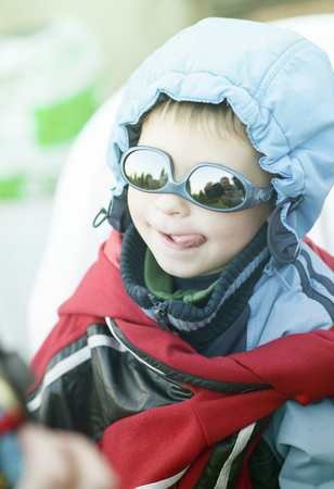 A boy in inverted sunglasses shows his tongue, portrait. emotion, pampering,