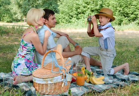 mily picnick on the outdoors. Family photo, boy with a camera Stock Photo