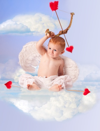 Cute angel baby with bow and arrow,  sitting on a cloud  Stock Photo