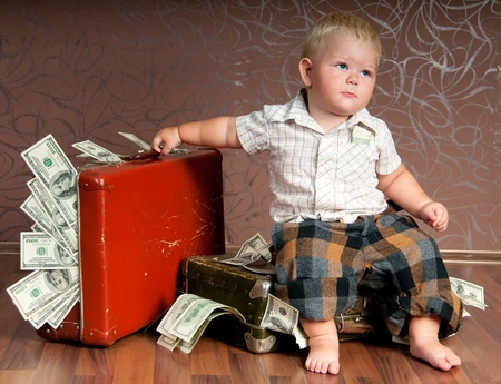 Cute little boy іs  sitting оn a suitcase with the money Stock Photo