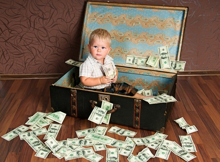 strongbox: Cute little boy іs  sitting in a suitcase with the money Stock Photo