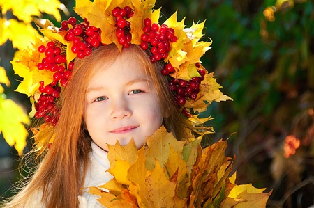 Cute smiling girl in a wreath of red viburnum on the head and with a bouquet of maple leaves in the hands