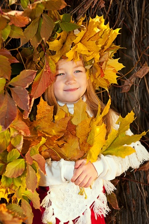 Cute smiling girl in a wreath of leaves on the head and with a bouquet of maple leaves in the hands