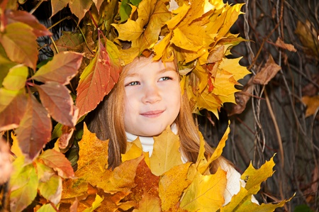 Cute smiling girl in a wreath of leaves on the head and with a bouquet of maple leaves in the hands photo