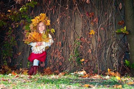 Linda chica sonriente en una corona de hojas en la cabeza y con un ramo de hojas de arce en las manos Foto de archivo - 11733536