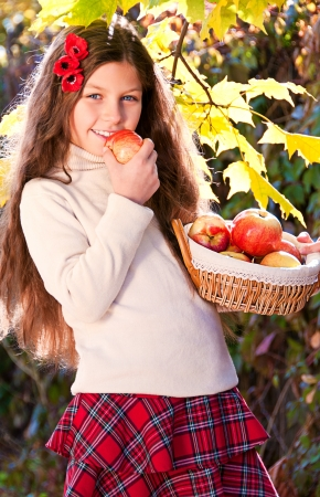 Beautiful long-haired brunette girl with red poppies in her hair and a basket of ripe apples in her hand