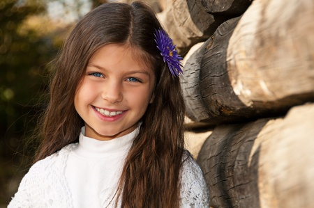 Lovely long-haired smiling girl against a wooden fence photo