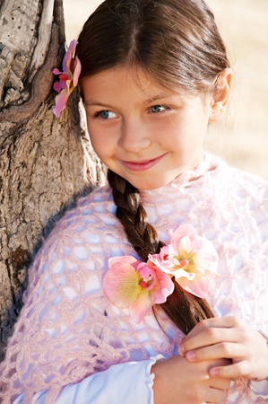 Portrait of a beautiful little girl with flower pink orchids in her hair. photo