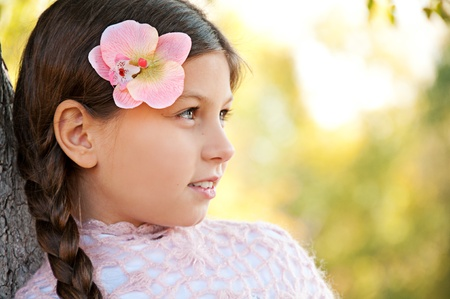Portrait of a beautiful little girl with flower pink orchids in her hair . photo