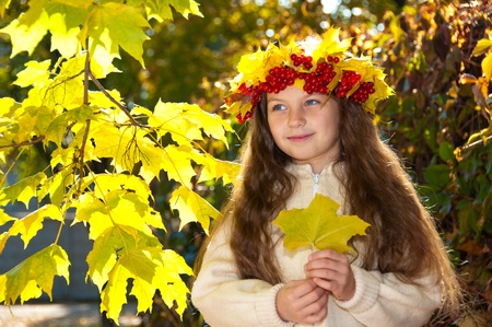 Cute smiling girl in a wreath of red viburnum on the head and with a  leave in the hands photo