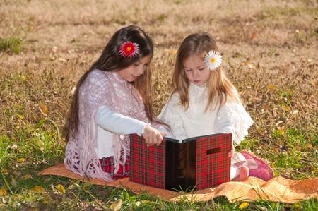 Dos niñas de leer el libro mientras está sentado en la hierba. Foto de archivo - 11733387