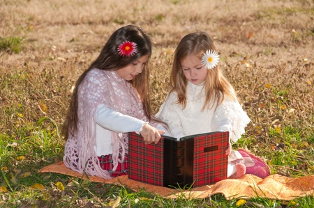 Two girls read the book while sitting on the grass. Stock Photo