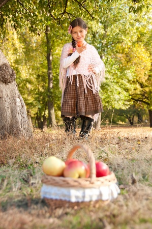 Beautiful long-haired brunette girl with flower pink orchids in her hair and a basket of ripe apples in her hand photo