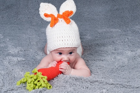 A small child with a rabbit ears  Lying on his stomach with a carrot  photo