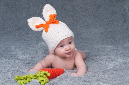 A small child with a rabbit ears  Lying on his stomach with a carrot  Stock Photo