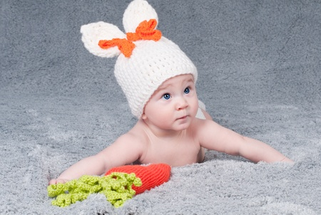 belonging to the caucasoid race: A small child with a rabbit ears  Lying on his stomach with a carrot  Stock Photo