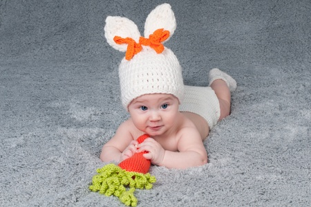 caucasoid race: A small child with a rabbit ears  Lying on his stomach with a carrot  Stock Photo