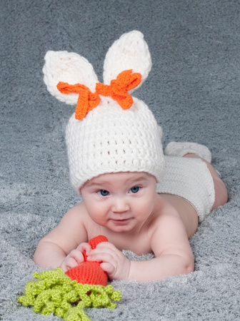 A small child with a rabbit ears  Lying on his stomach with a carrot Stock Photo - 12636824