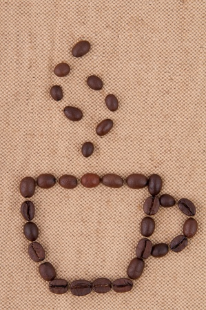 A cup of coffee beans with smoke on the background of burlap  photo