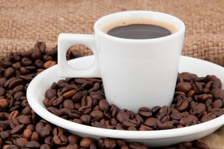 A cup of coffee on the background of coffee beans photo