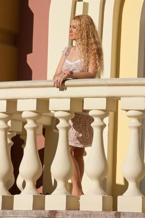 A beautiful young blond sexy woman standing near the railing  photo