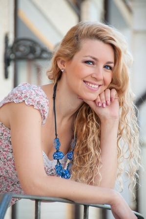 mackintosh: A beautiful young blond sexy woman standing near the railing