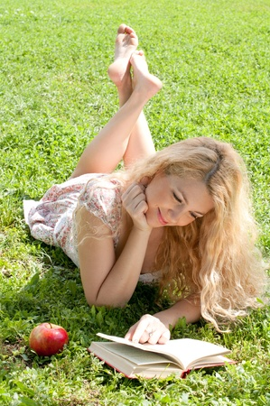 Beautiful young woman reads book, on green summer background  Stock Photo